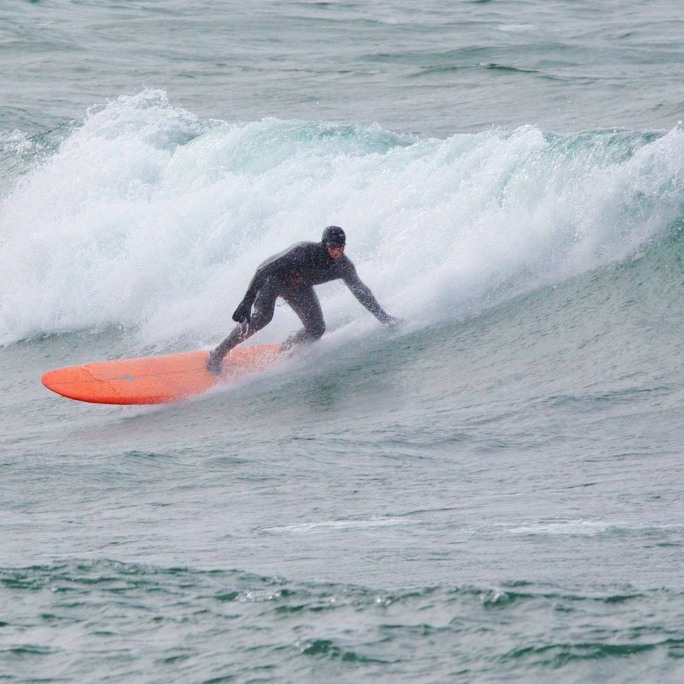 Keith catching a wave on Lake Superior in a wet suit